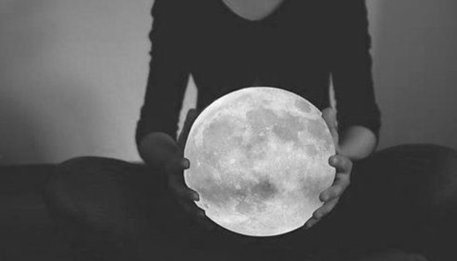 Woman holding the Full Moon